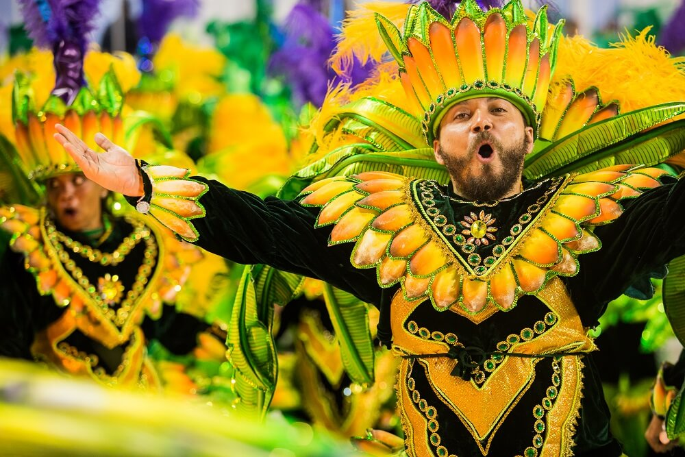 Cheerful guy parading in a samba school costume